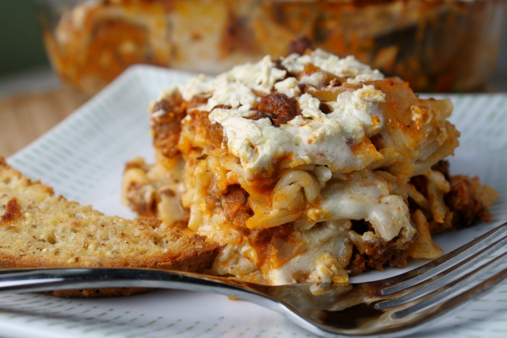 horizontal close up  image of gluten free noodle casserole layered with red meat sauce, cheese mixture, on a white plate with a fork