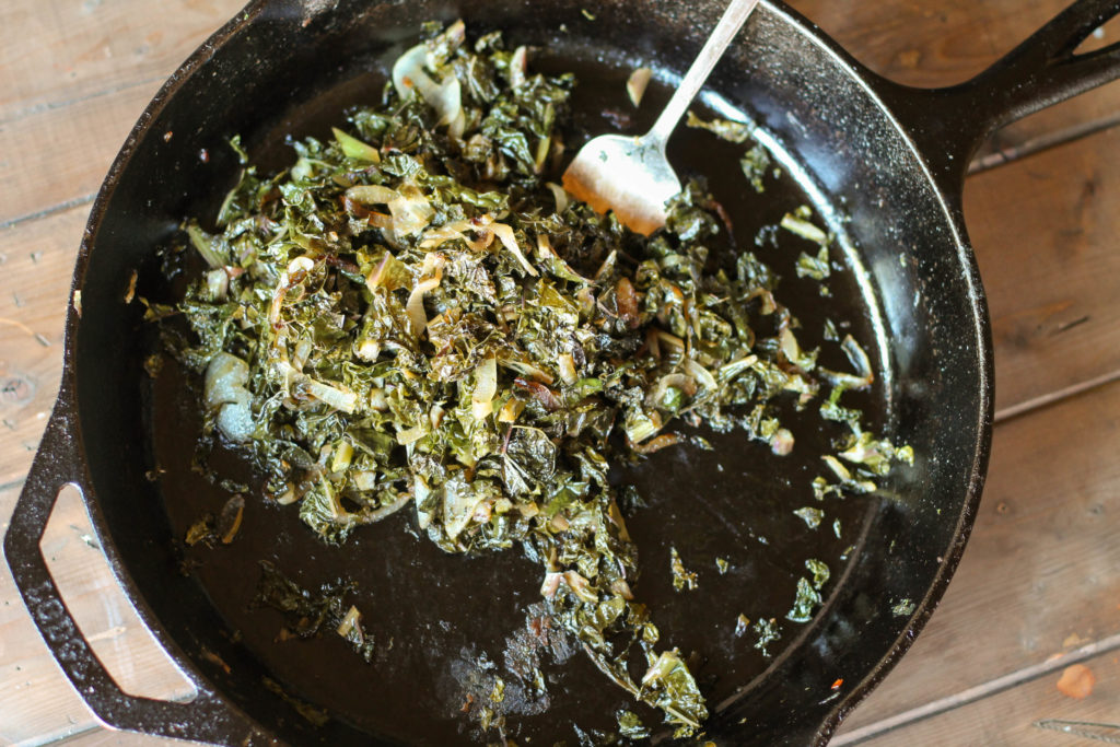Sauteed Kale w Caramelized Onions in a cast iron pan one a wooden a pallet from overhead