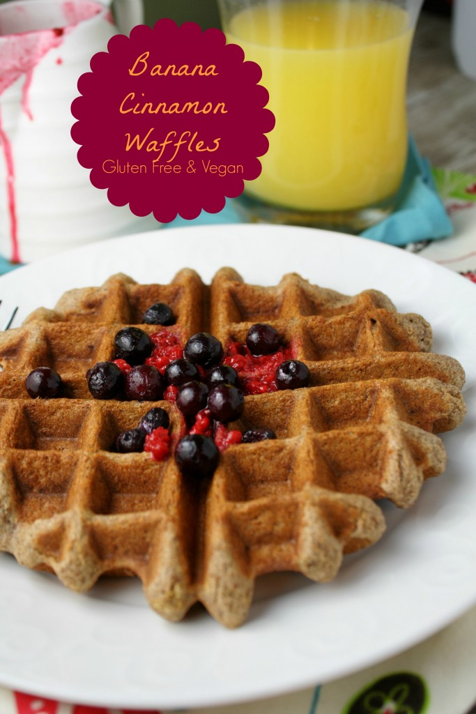 golden brown waffle topped with raspberry puree and fresh blueberries on a white plate with a glass of orange juice in the background