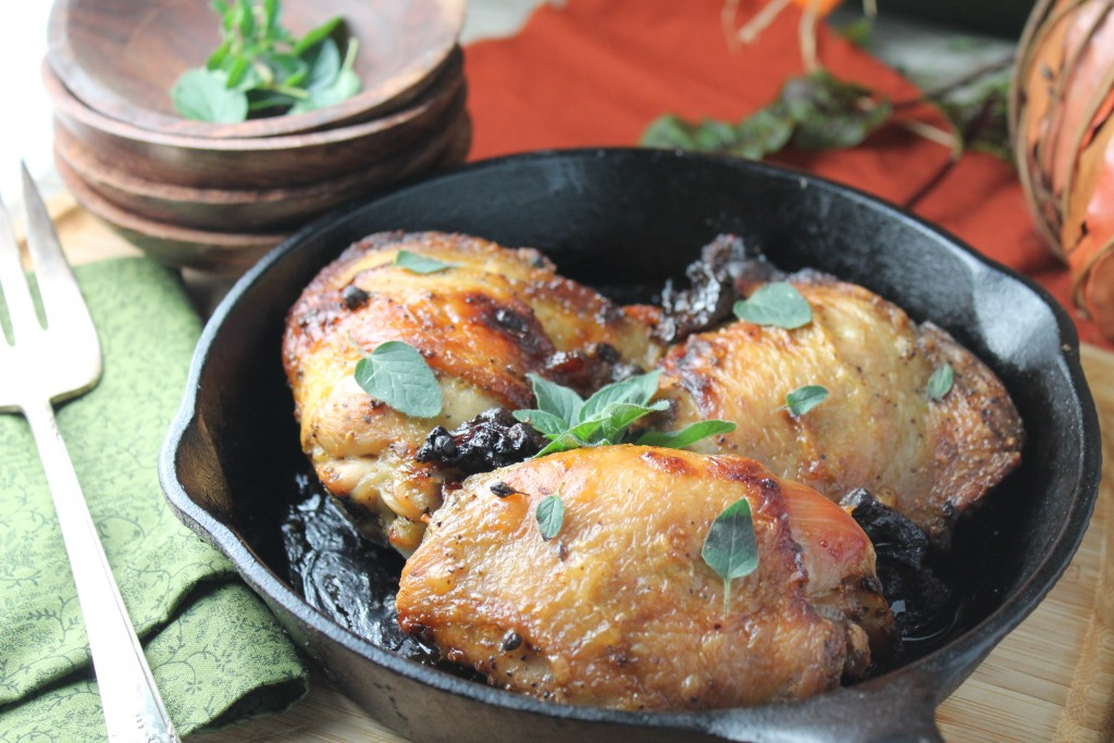 a cast iron pan filled with three bone-in chicken thighs with crunchy skin and an oregano and prune garnish
