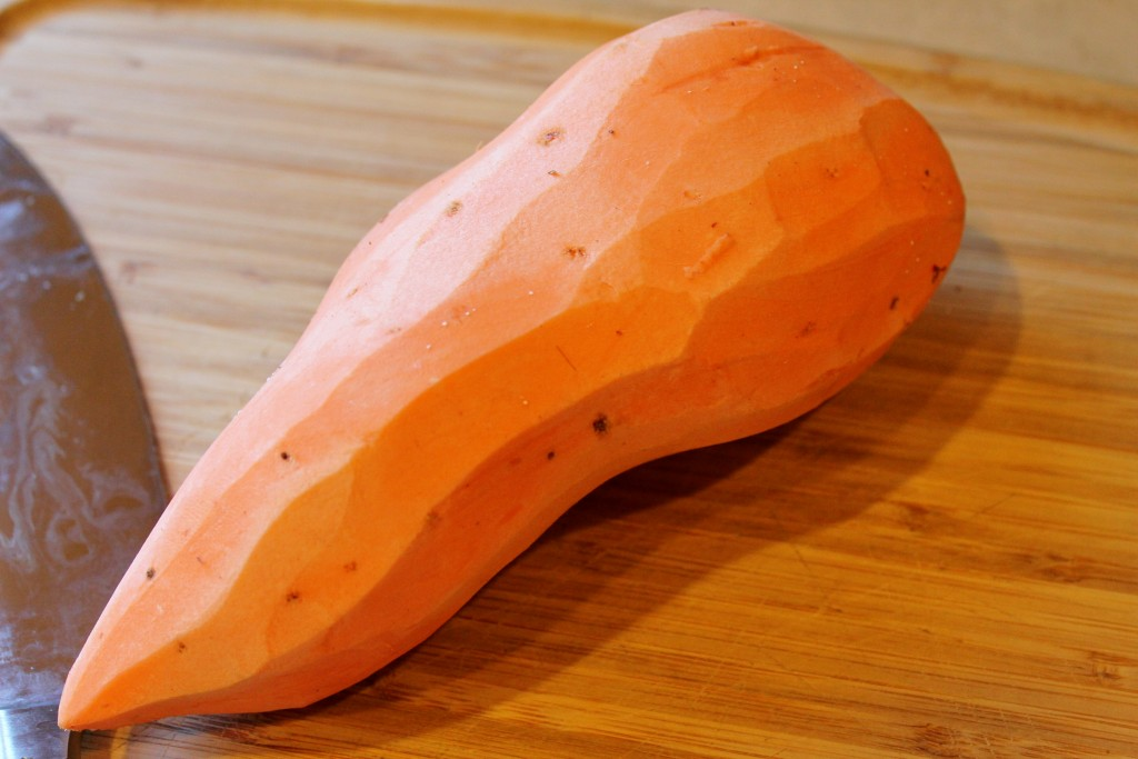 peeled sweet potato on a wooden cutting board