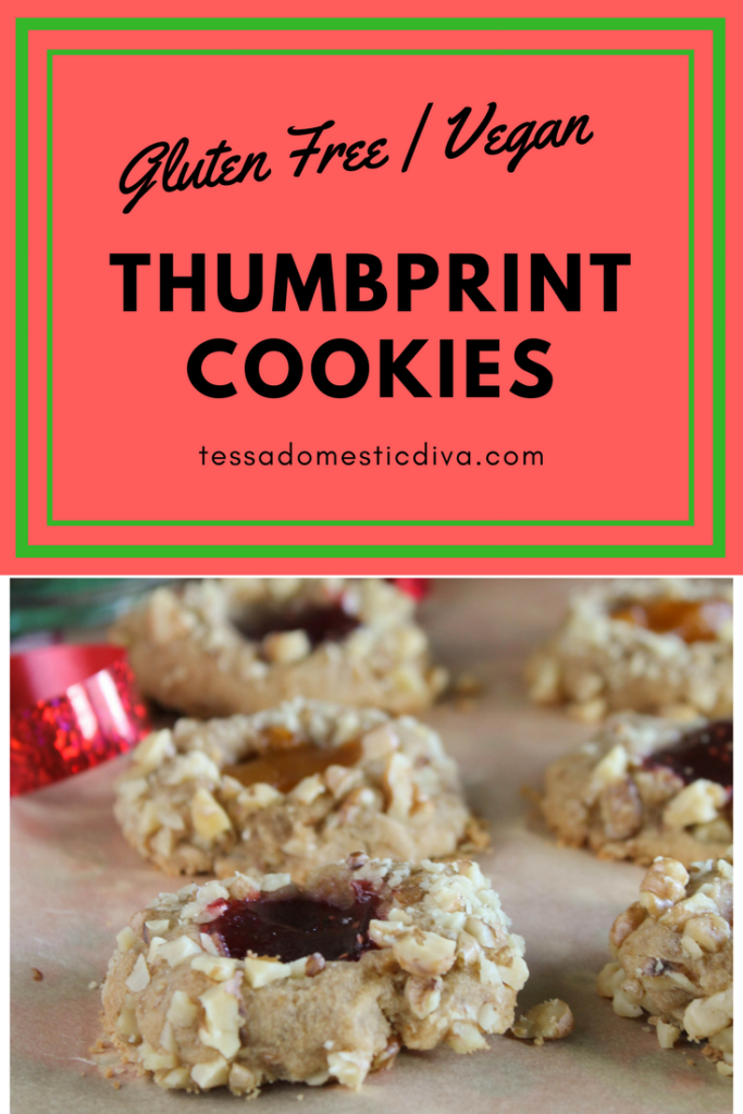 pinterest ready eye level image of berry and apricot jam filled thumbprint cookies with a a walnut coating on a piece of parchment with Christmas ribbons