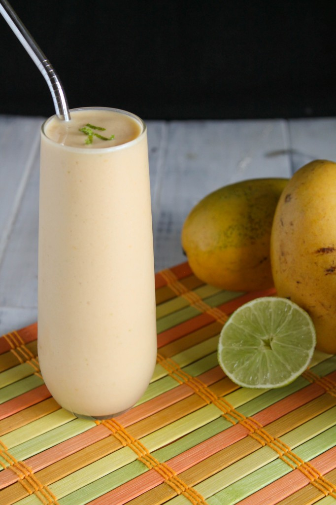 frosty orange mango lime kombucha smoothie with a wedge of lime and thai mangoes
