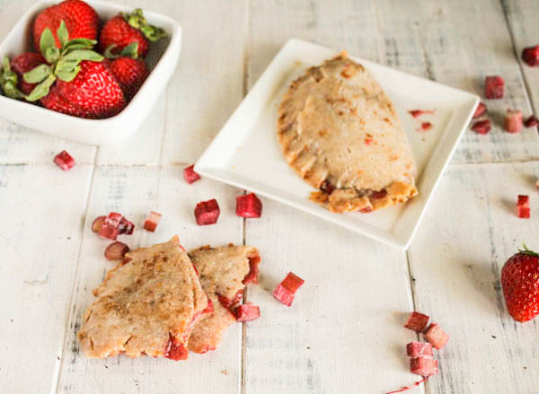 overhead shot of strawberry rhubarb hand pies arranged on a white washed board with diced fresh rhubarb and fresh whole strawberries
