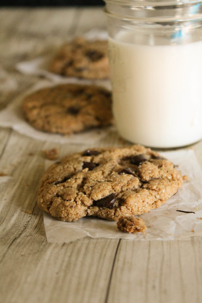 vertical image of cashew chocolate chip cookies with glass of milk in a mason jar in background