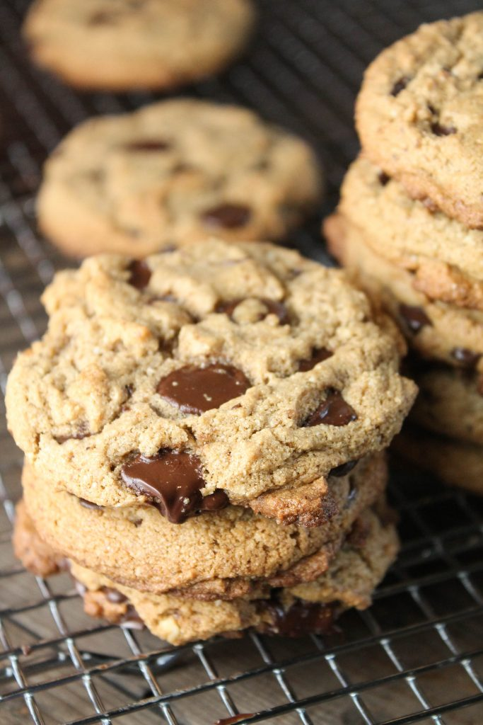 vertical image of 3 stacked best paleo chocolate chip cookies with melty chocolate on a metal cooling rack