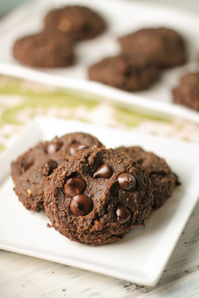 vertical image of 3 double chocolate cookies plated on a white plate and more cookies in background
