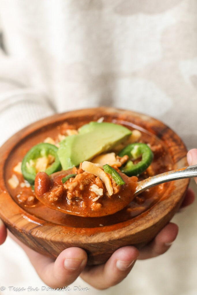 hand held wooden bowl filled with chili and topped with frash avocado, cilantro, and cheese