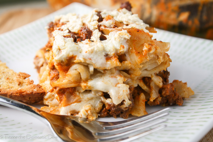 a square of noodle casserole layered with a creamy white cheese sauce and red meat sauce atop a white plate
