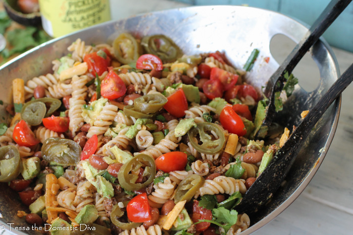 a silver bowl to a tex-mex pasta salad prepared and ready to serve with two wooden spoons