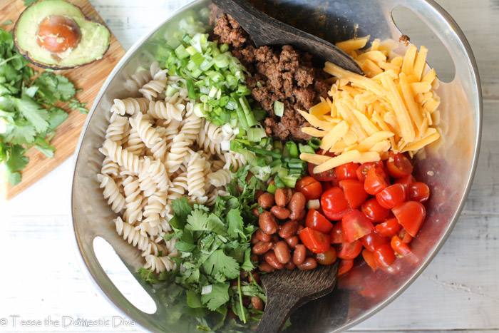 a birds eye view of a a tex mex pasta ingredients separated and ready to toss