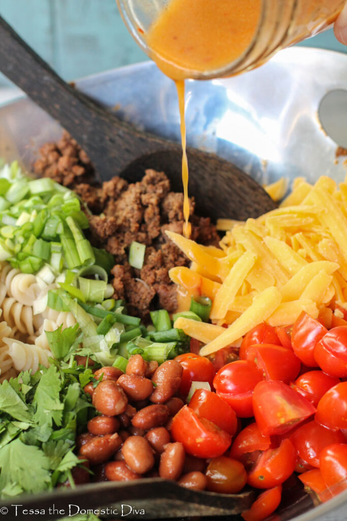 a chipotle vinaigrette being poured over the top of pinto beans, fusilli noodles, cheese, tomatoes, taco meat, cilantro, and green onions