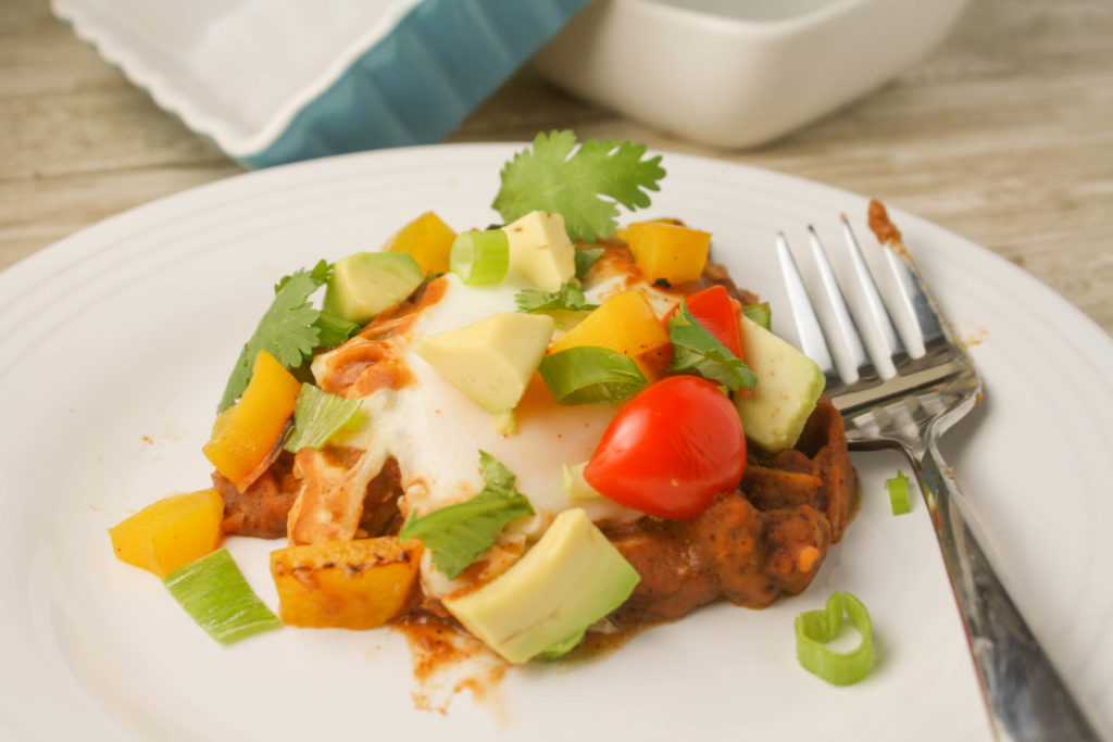 a white plate with a fork filled with refried bean and a molten poached egg with cilantro, tomato, and avocado garnishes