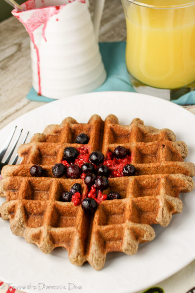 a golden waffle atop a white plate with fresh berries on top