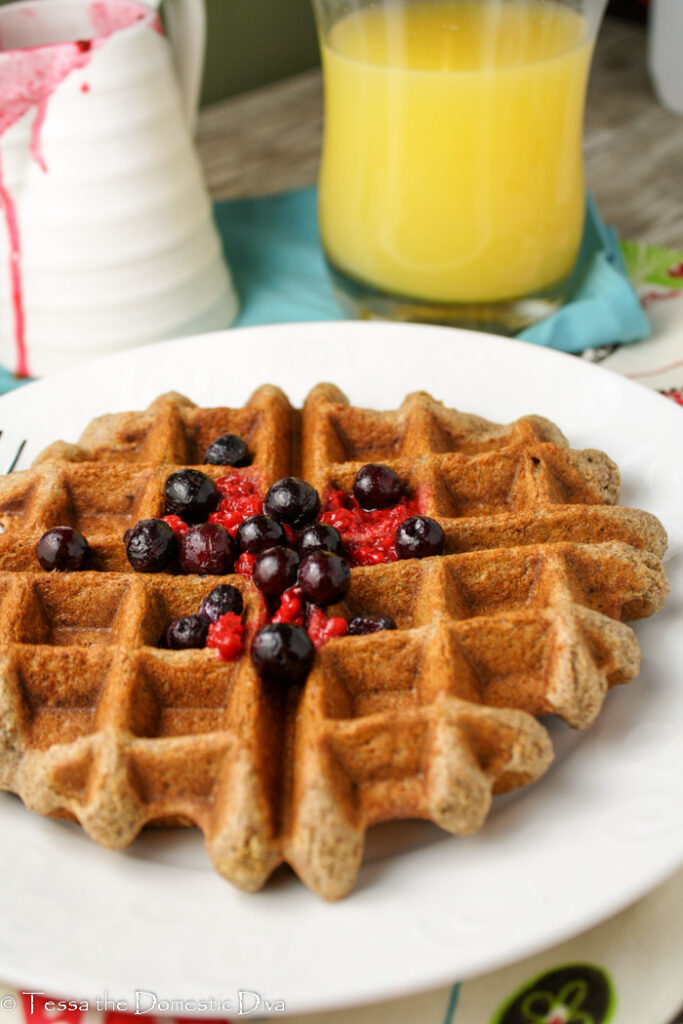 front view of a golden brown waffle with fresh berries, orange juice, and a pitcher of syrup