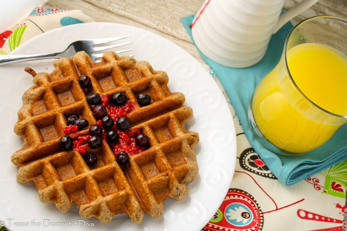 birds eye view of a wholegrain gluten free waffle on a white plate with fresh berries