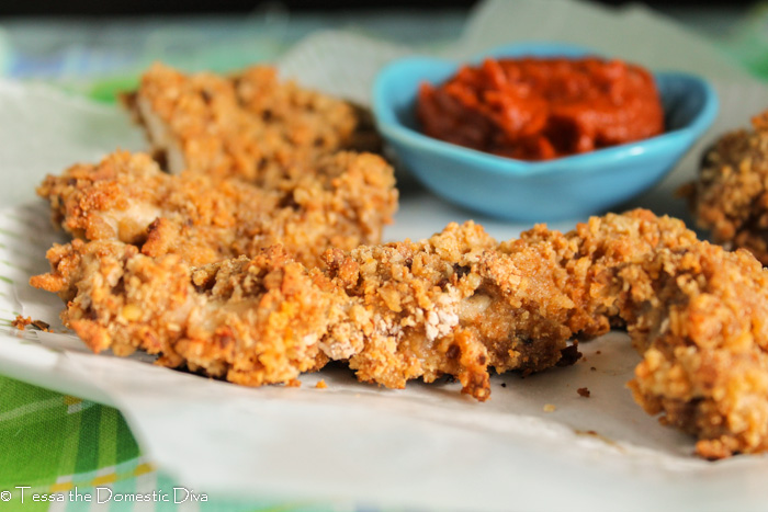 crispy oven fried chicken tenders on a piece of parchment paper with a dish of ketchup