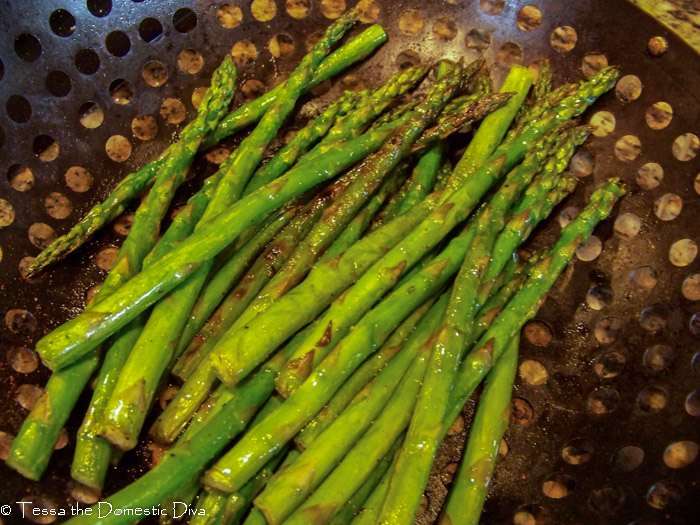 birds eye view of a grill basket filled with grilled asparagus
