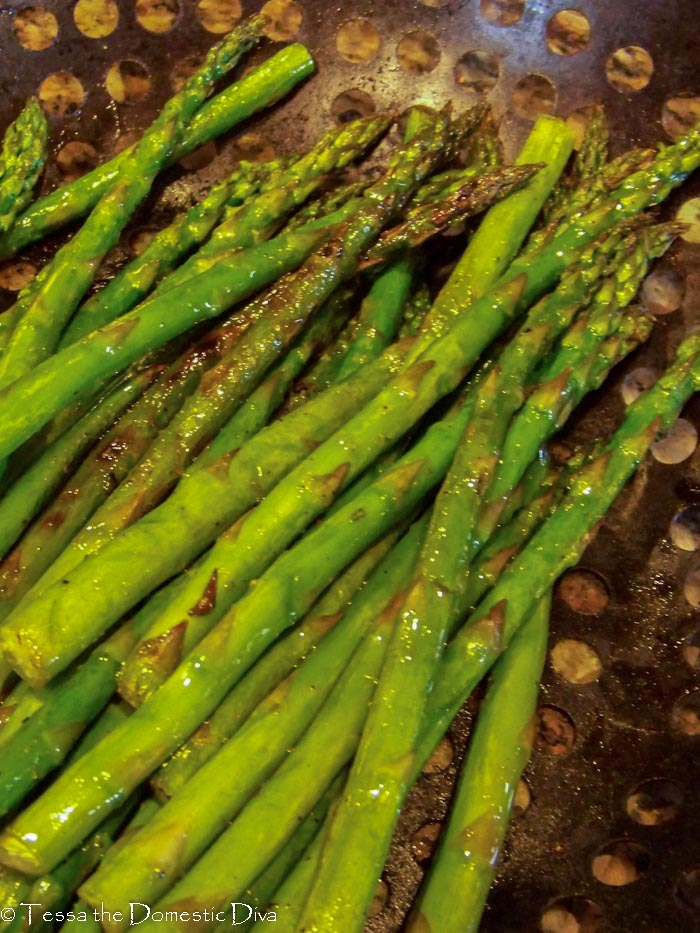 from above view of a black grill basket with grilled asparagus spears