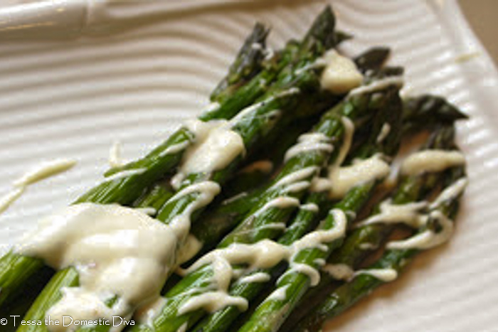 close up of grilled asparagus with a garlic lemon aioli drizzle