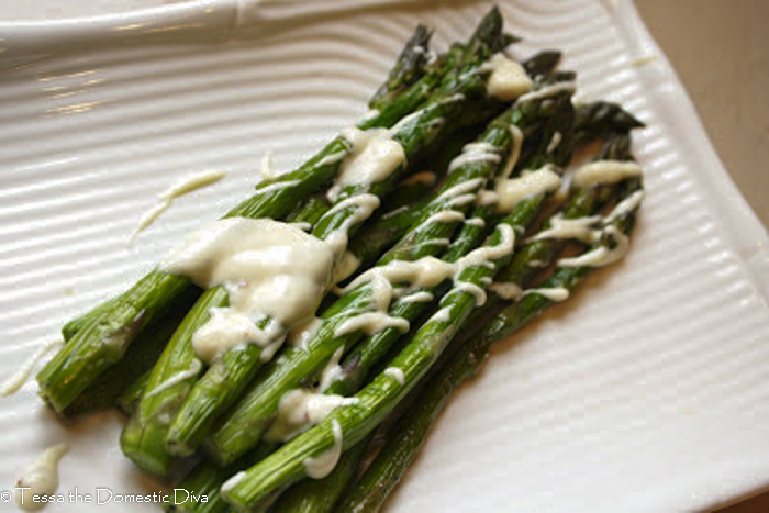 a white plate with many grilled apsaragu stalks with a creamy white drizzle