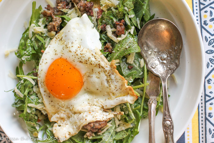 birdseye view of a white bowl filled with mized greens in a lemon dressing and topped with a fried egg with a molten yolk and sausage