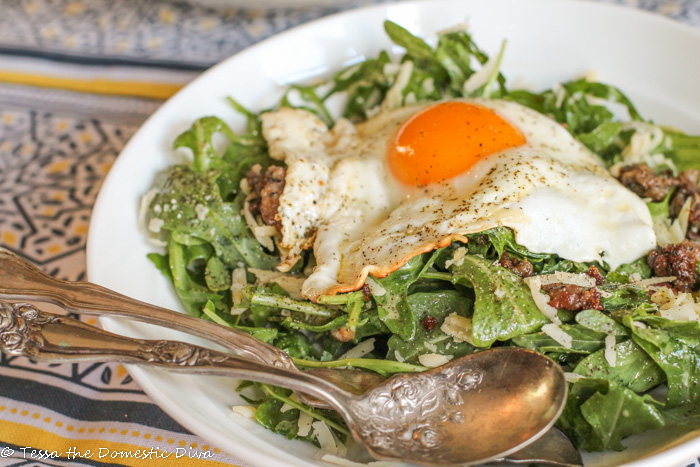 an egg with a molten yolk draped over a dressed salad with ground cooked sausage and white cheese shreds
