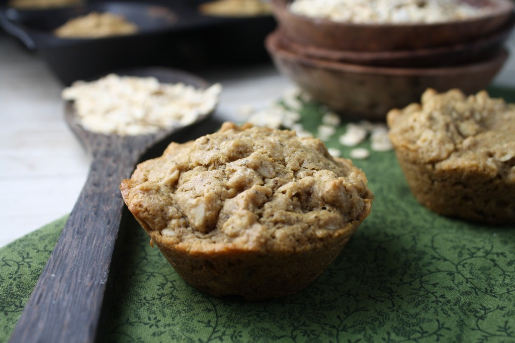 close up of a oatmeal studded muffins on a forest green cloth with a stack of wooden bowls in the background