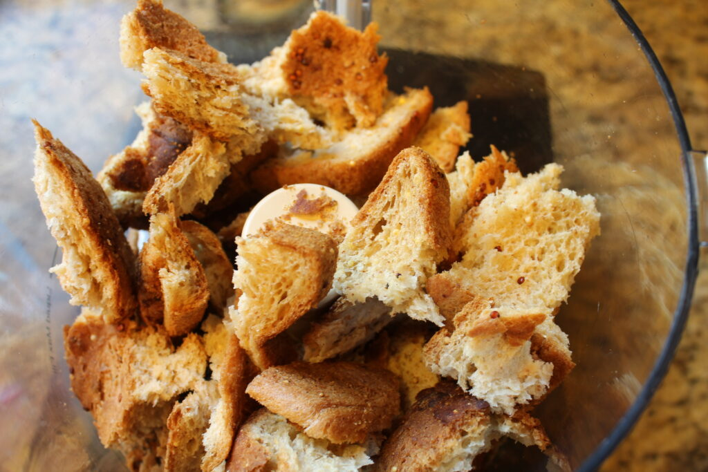torn pieces of stale gluten free bread in a food processor bowl