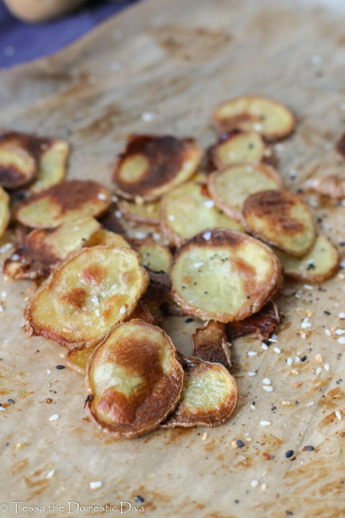 a pile of golden crispy slices of potatoes on parchment paper.