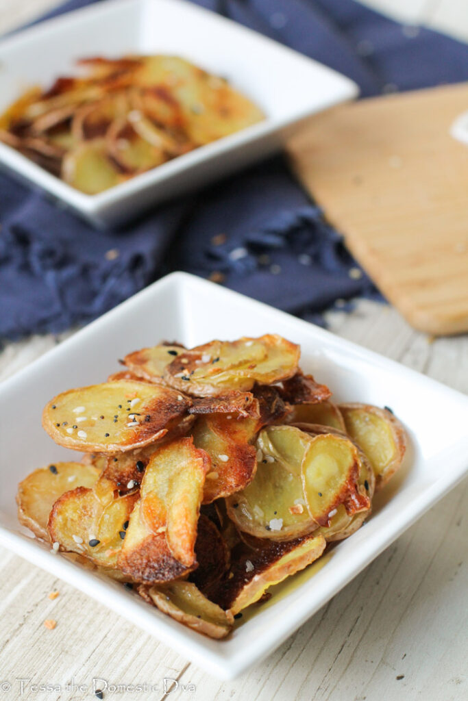 two white bowls filled with sliced roasted potatoes.