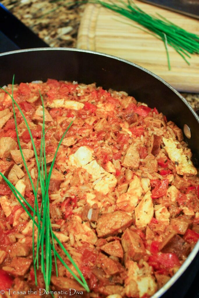 a skillet with filled with jambalaya topped with fresh chives