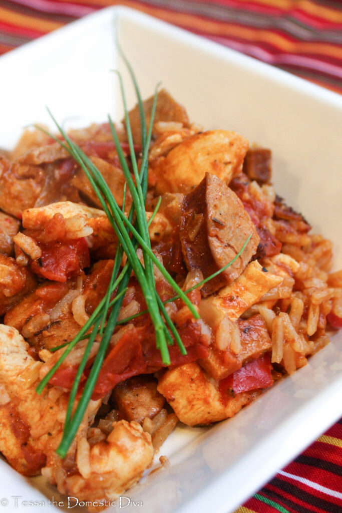 a square white bowl filled with a cajun rice, chicken, and sausage dish cooked in a tomato sauce