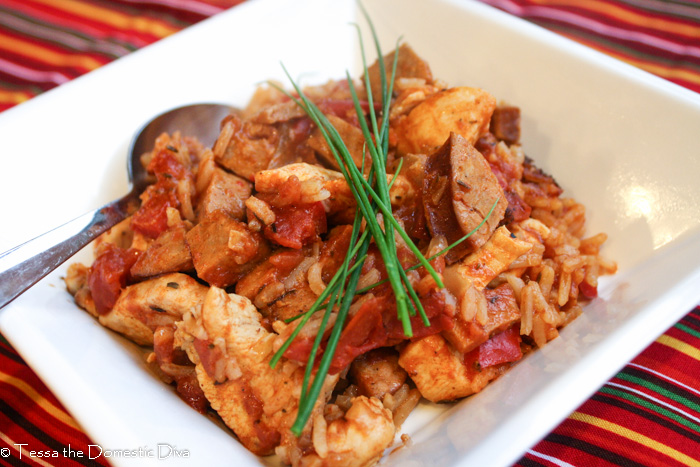 a sqaure white dish with a cajun tomato rice, chicekn, and sausage dish topped with fresh chives