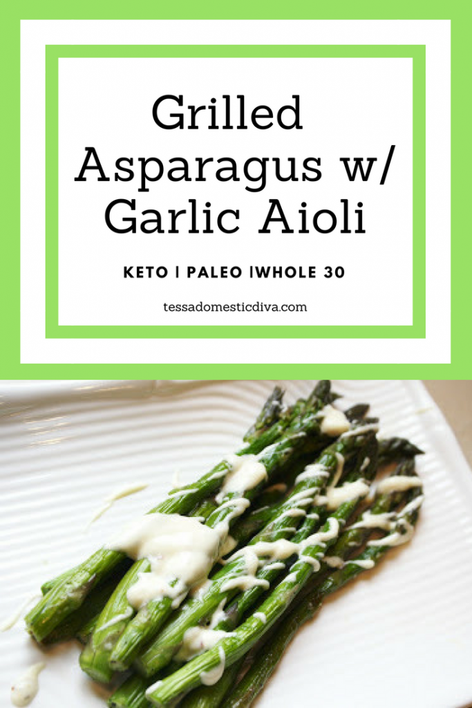 grilled asparagus on a white plate with a mayo drizzle looking from above
