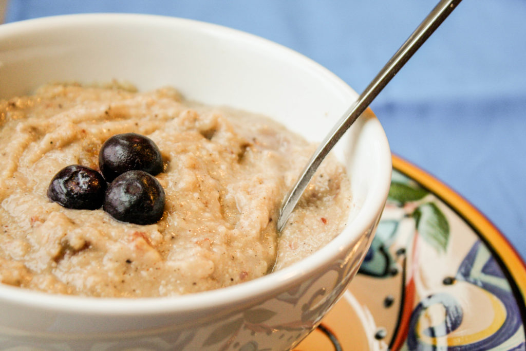fron view of a white bowl filled with millet porridge and fresh berries with spoon and blue background