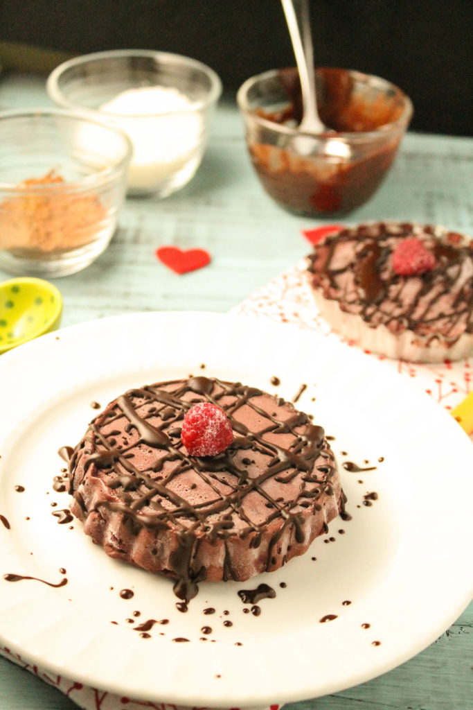 a small chocolate raspberry tart on a white plate with chocolate drizzle