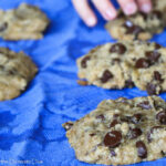 chococlate chip cookies arranged on a blue cloth with a child's hand reaching for a cookie