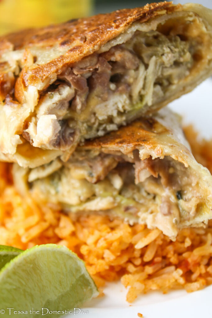 close up up of a halved baked chimichanga filled with beans, Spanish rice, and chicken