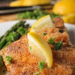close up view of two pan fried breaded fish pieces on a white plat with lemon and parsley