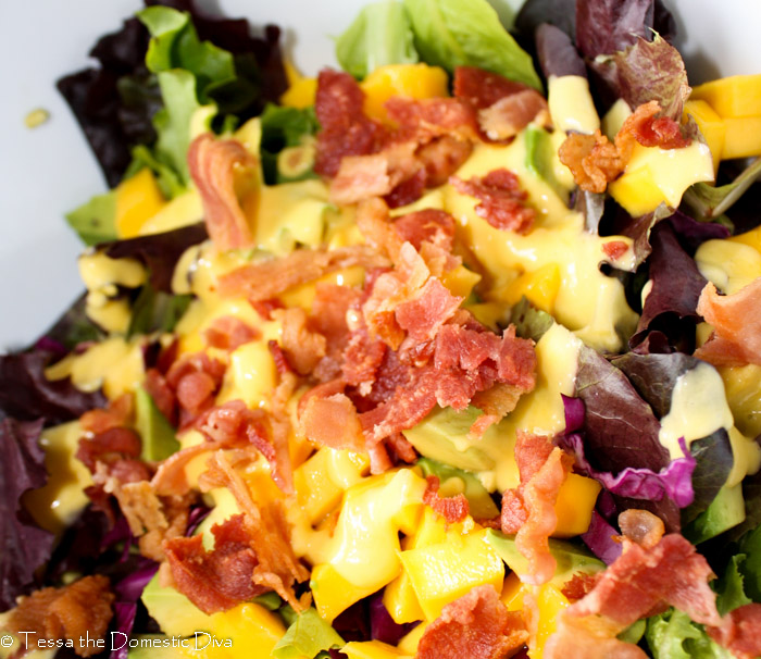 vibrant yellow mango vinaigrette drizzled on a mixed greens and bacon salad