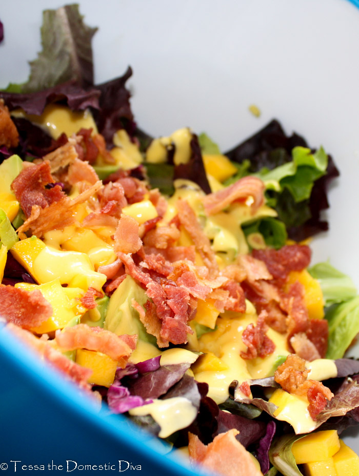 a blue bowl filled with mixed greens topped with mango dressing and chopped bacon