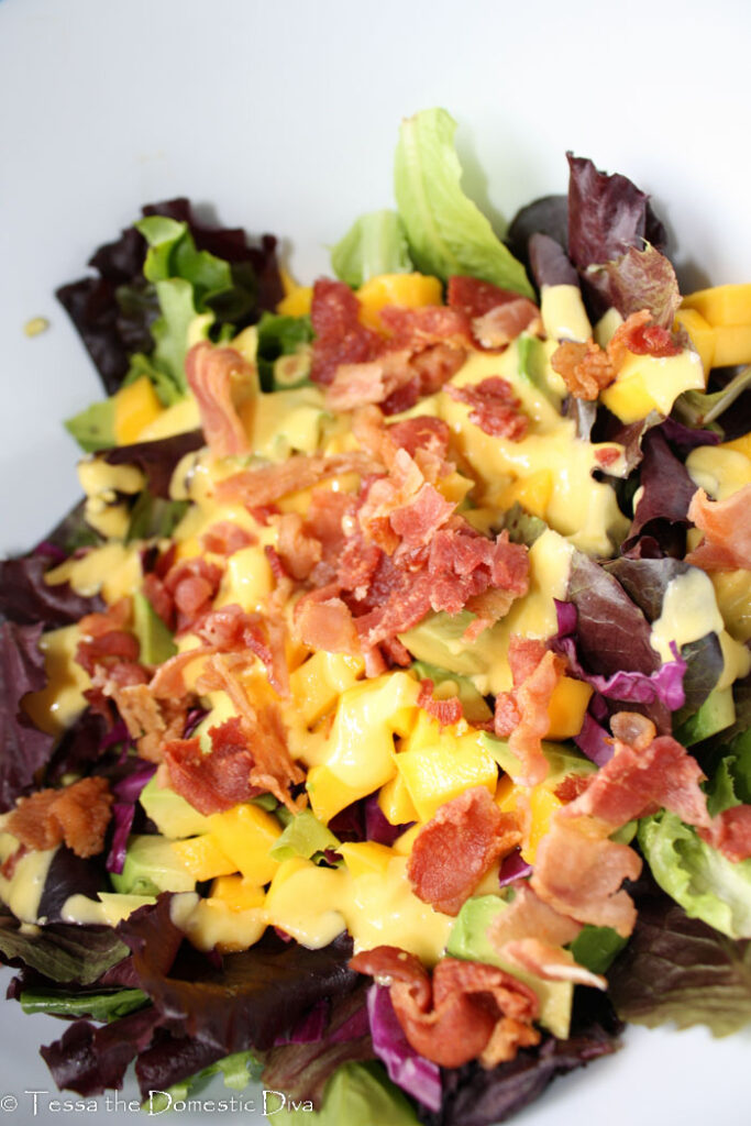 mixed green topped with a bright yello mango vinaigrette and bacon chunks