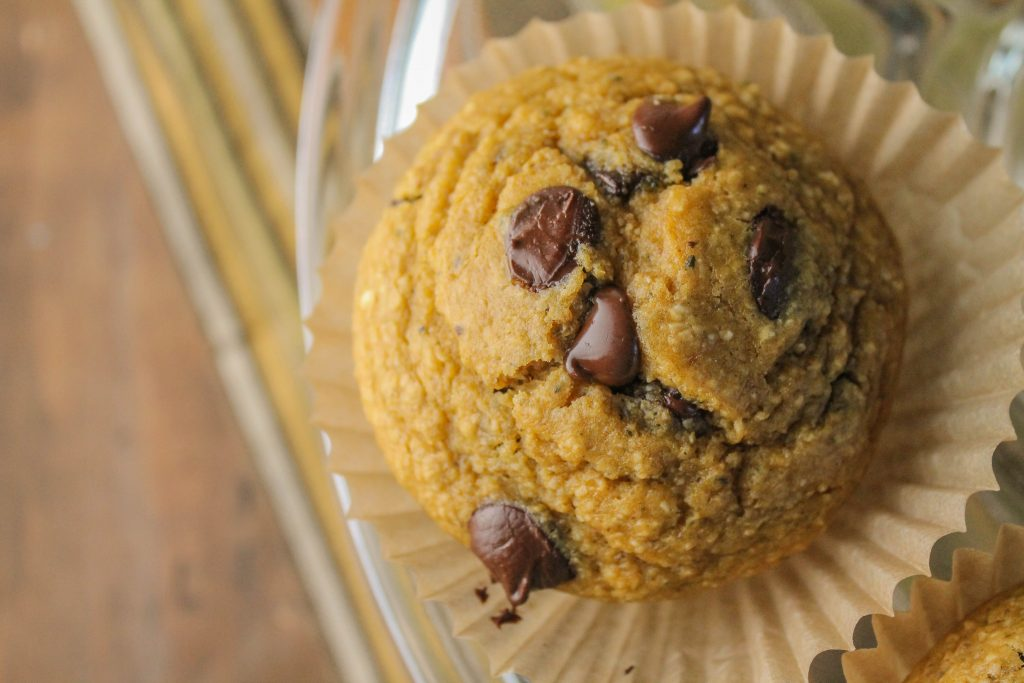 overhead close up of one hocolate studded pumpkin hemp oat muffin in a natural baking cup