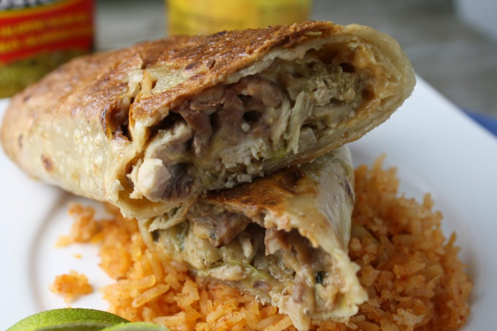 horizontal image of sliced crispy and golden brown rice tortillas filled with a creamy chicken, refried bean, rice, and cheese filling