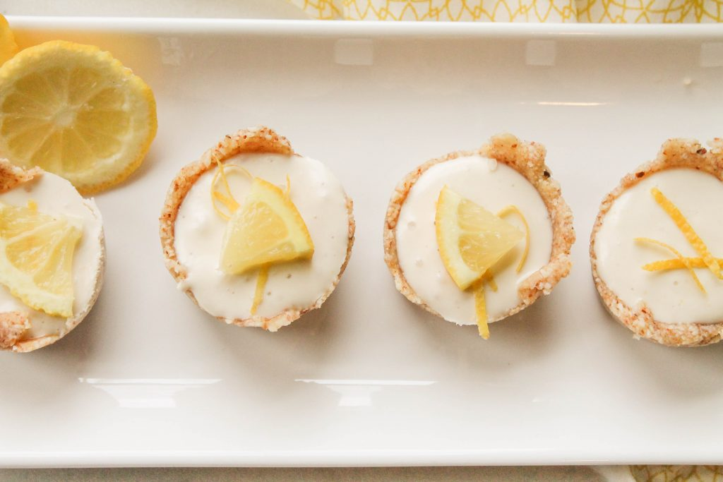 4 creamy lemon cheesecake tarts on a white plate with lemon slice garnish