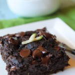 a square of moist chocolate zucchini cake topped with gooey chocolate chips and a few fresh zucchini shreds