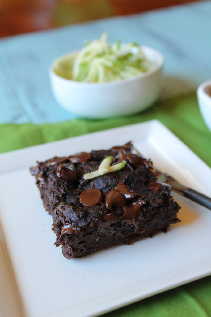 dark chocolate square of zucchini cake with melty chocolate chips and a a garnish of fresh zucchini on a white plate