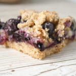 close up of a triangle slice of blueberry filled crumble bars