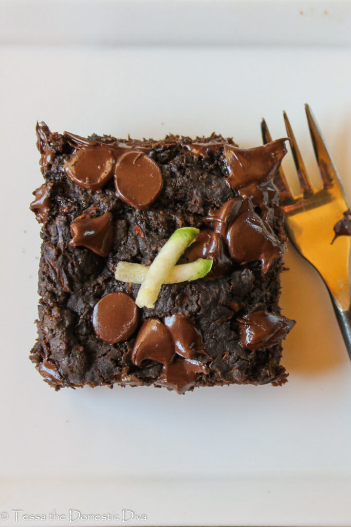 birds eye view of a chocolate chip studded chocolate cake square on a white plate.